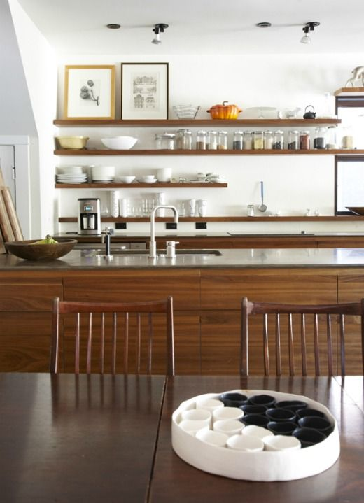 a mid-century modern kitchen with no uppers, open shelving, a large kitchen island and artworks