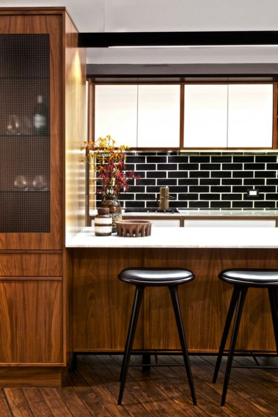 a mid-century modern kitchen with a large wooden kitchen island with a white countertop, black stools, a black tile backsplash