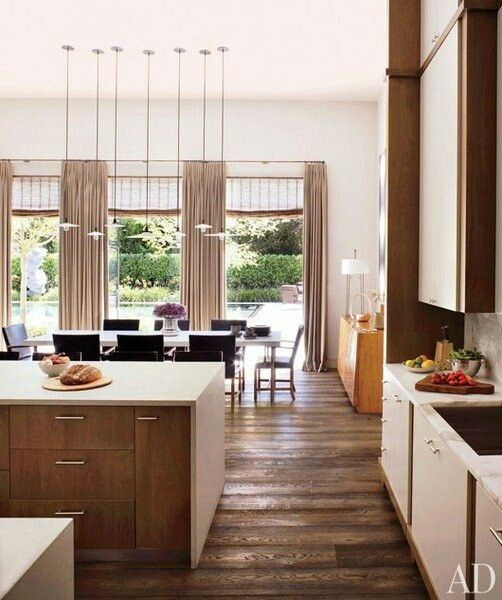 a white and rich-stained mid-century modern kitchen with neutral countertops and hardwood floors