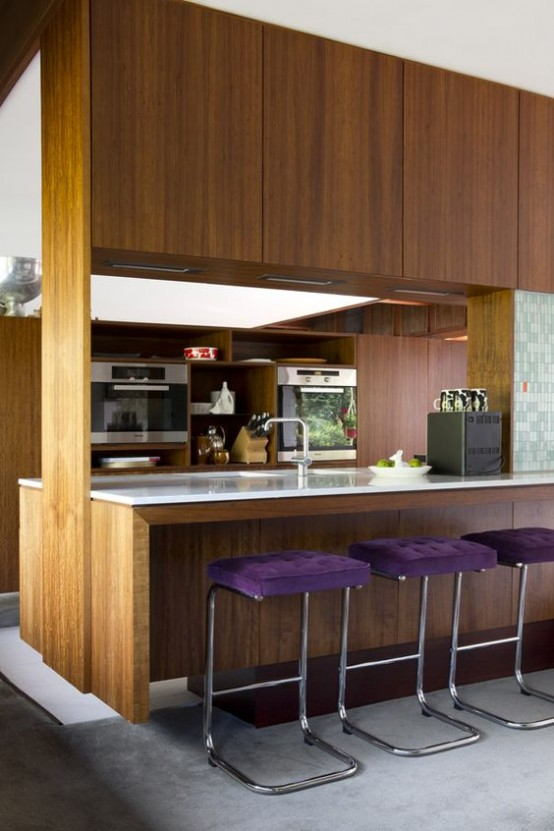 a contemporary meets mid-century modern kitchen with rich-stained cabinets, white countertops and purple upholstered stools