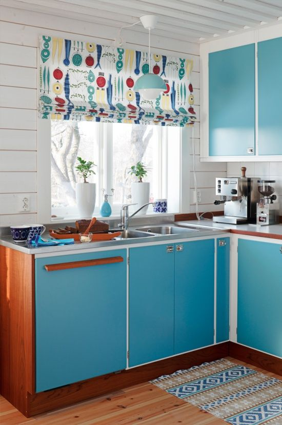 a bright blue mid-century modern kitchen with colorful Roman shades, touches of rich stained wood