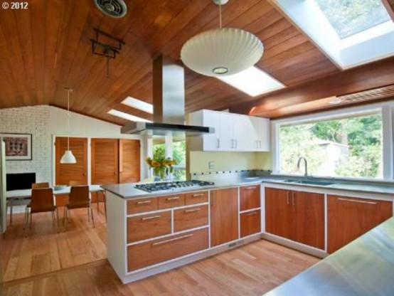 a bright mid-century modern kitchen with wooden cabinets, white countertops, skylights and a window backsplash