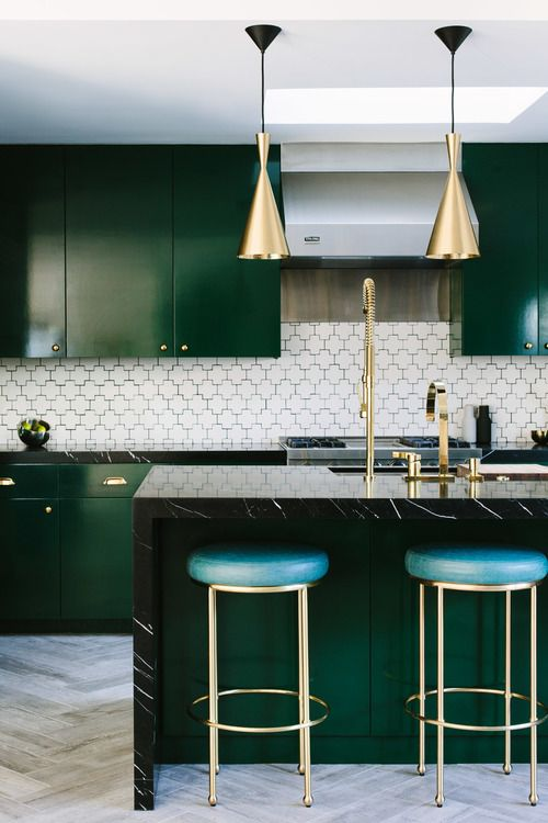 an elegant dark green kitchen with brass pendant lamps, leather and brass stools and a mosaic tile backsplash