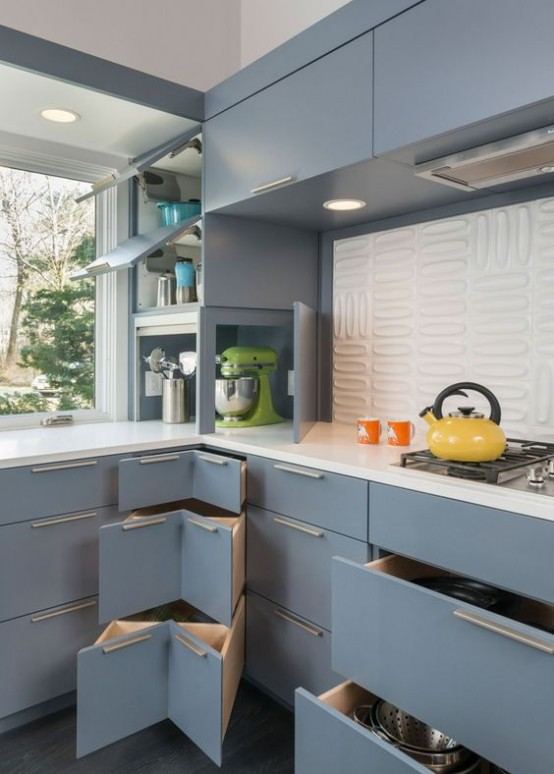 a light blue mid-century modern kitchen with white countertops and a white textural tile backsplash