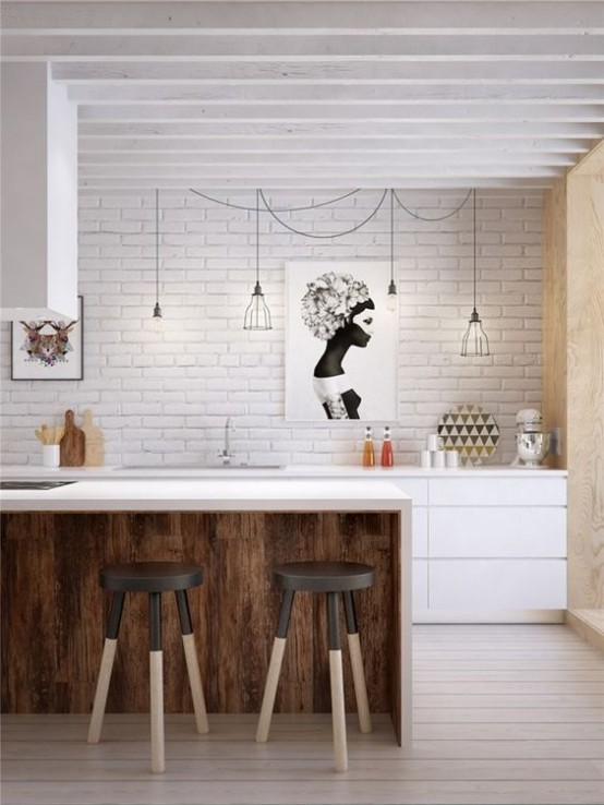 a mid-century modern meets industrial kitchen with a white brick wall, a white kitchen island with stools, black wire pendant lamps
