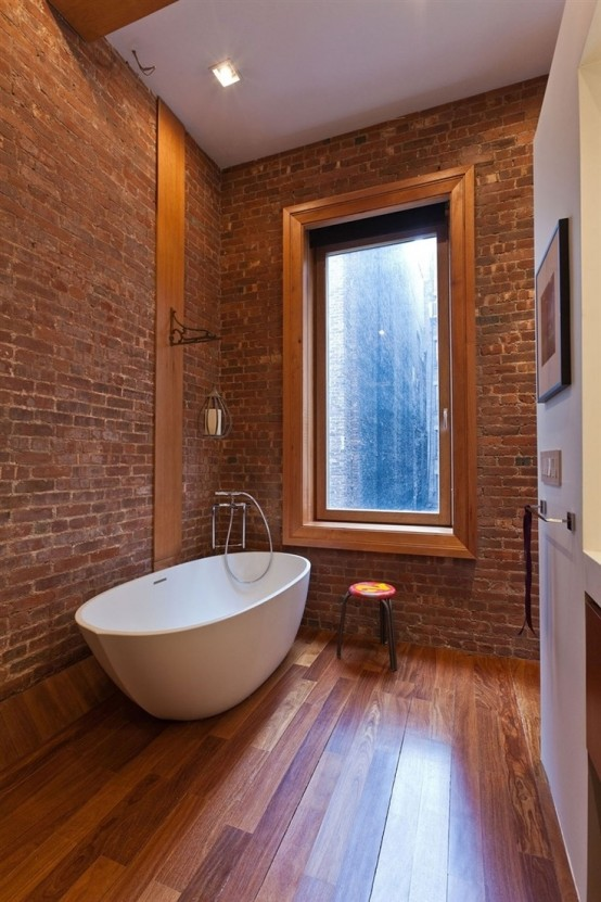 a laconic modern bathroom with brick walls, a laminate floor, a large window and a stool - nothing else is needed here