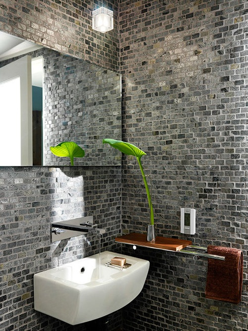 a bathroom or a powder room with grey brick walls, a curved sink, a mirror and a modern mini shelf