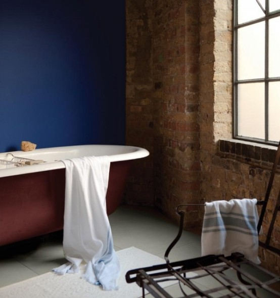 a bold bathroom with red brick walls, a statement blue wall, a red bathtub, a wire chair