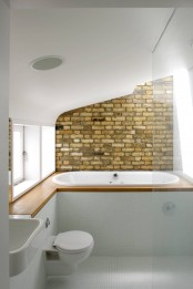 a laconic bathroom with white tiles, a built-in bathtub, a brick accent wall, a sink and toilet