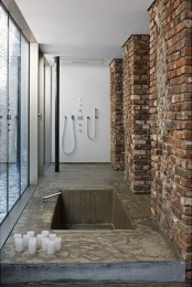 a minimalist bathroom with brick walls, a built-in tub or shower space of concrete and lots of candles