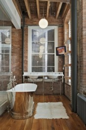 an industrial bathroom with red brick walls, a shiny metal tub, windows and a double vanity with a vintage feel