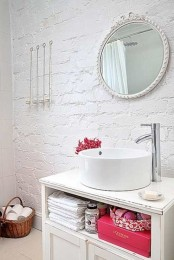 a white bathroom with brick walls, a round mirror, an open vanity, a basket for storage and colorful accents