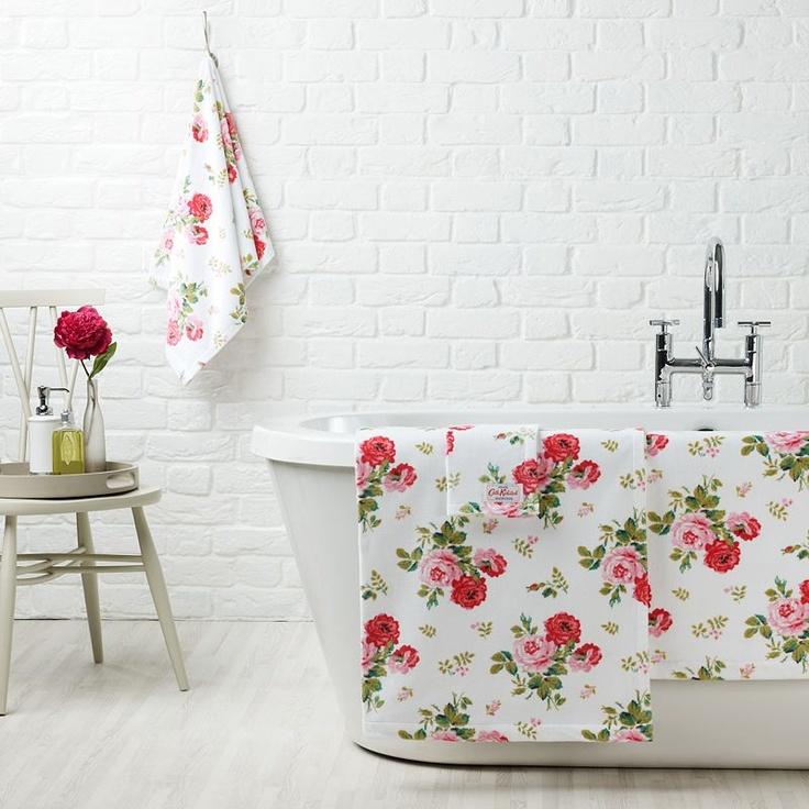 a cute white bathroom with a brick wall, a modern bathtub, colorful textiles and a small stool
