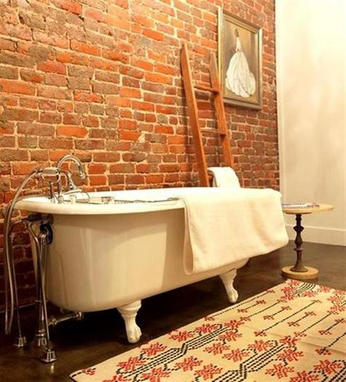 a vintage-inspired bathroom with a red brick wall, a colorful rug, a ladder, a side table and an artwork