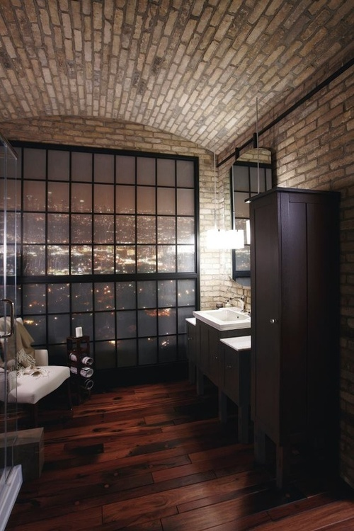 a contemporary bathroom doen with white brick walls, dark furniture, a shower, a vanity with a sink and an arched ceiling