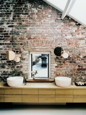 a modern bathroom with a red brick wall, a window, a long vanity with two sinks and a frosted glass roof