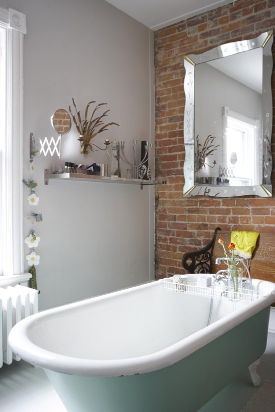 a whimsy bathroom with a brick wall, a pastel green tub, a vintage-inspired mirror and some modern stuff
