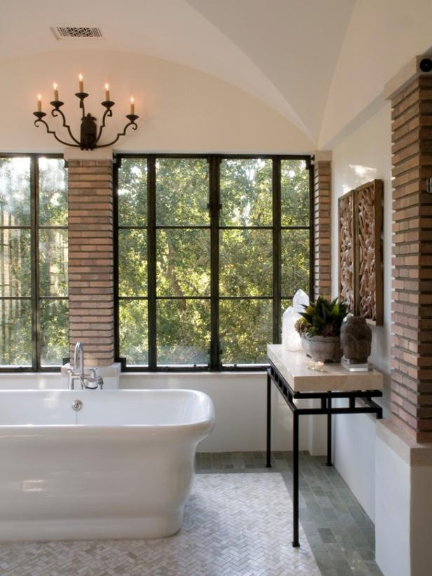 a modern bathroom with brick walls, large framed windows, a tiled floor, a large tub and a chic chandelier