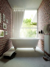 a gorgeous small bathroom with red brick walls, a glazed wall, a vintage-inspired tub and a gallery wall