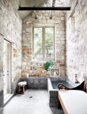 an indoor-outdoor bathroom with brick walls, a stone tub, a carved wooden bench, windows and a door