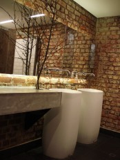 a coontemporary powder room done with a red brick wall, a concrete vanity, free-standing sinks and an oversized mirror