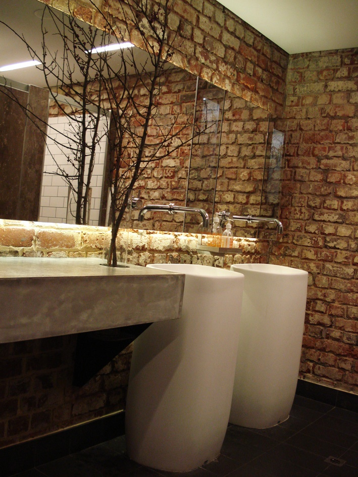 a coontemporary powder room done with a red brick wall, a concrete vanity, free standing sinks and an oversized mirror