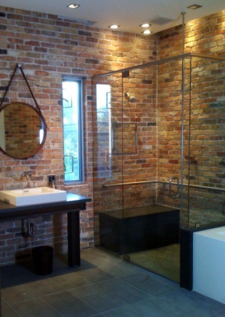 a contemporary bathroom with red brick walls, a glass shower space, a dark vanity and a large round mirror