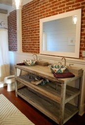 a vintage rustic bathroom with a faux red brick wall, a shabby chic wooden vanity, an oversized framed mirror and a shower space