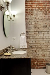 a vintage powder room with whitewashed brick walls, a stone countertop vanity, wall lamps, a round mirror looks catchy