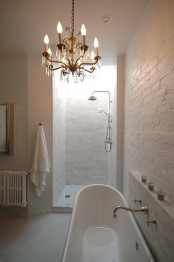 a neutral bathroom with white brick walls, a vintage tub, a crystal chandelier, a shower space also done with bricks
