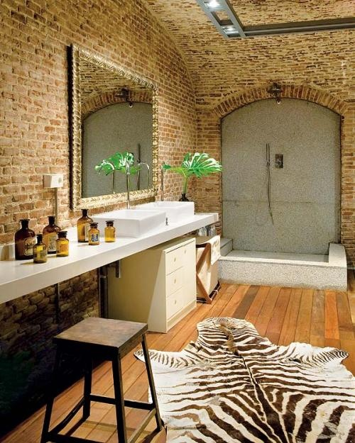 a bold and whimsy bathroom with brick walls, a long vanity with a sink and a mirror, a shower space done with stone and a faux animal skin