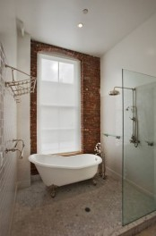 an eclectic bathroom with a brick wall, white subway and marble tiles, a shower space and a vintage tub