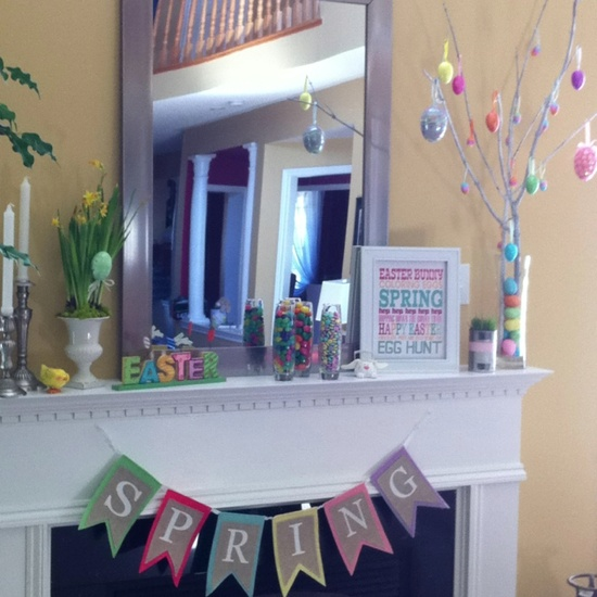 an Easter tree with colorful eggs, a bright bunting, daffodils in a pot, colorful letters and bright candies in a jar