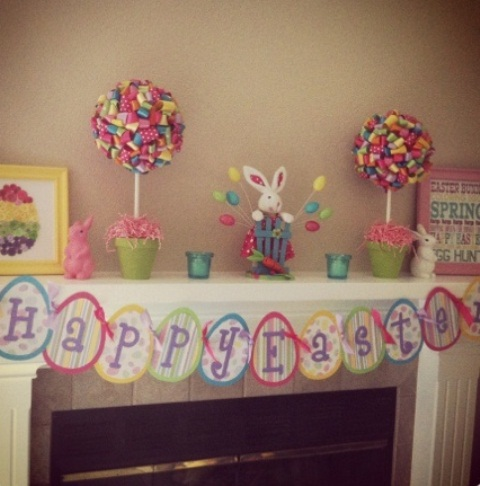 a bright Easter mantel with colorful paper topiaries, bunny figurines and a colorful bunting