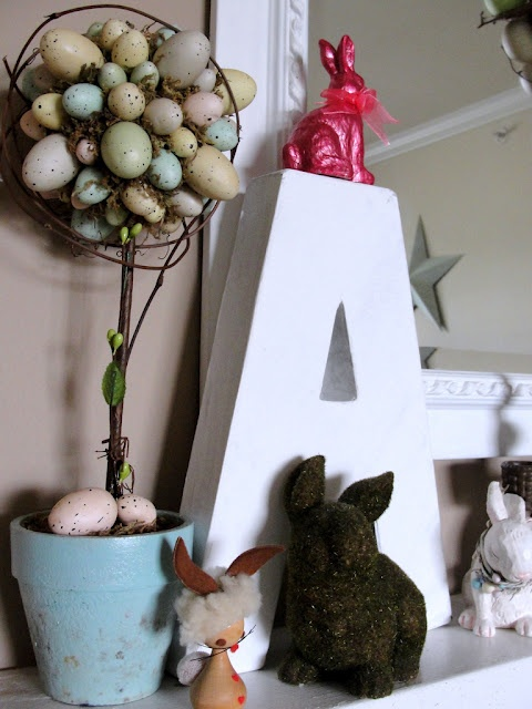 a pastel speckled egg Easter topiary, bunny figurines and a monogram is a simple mantel decor idea