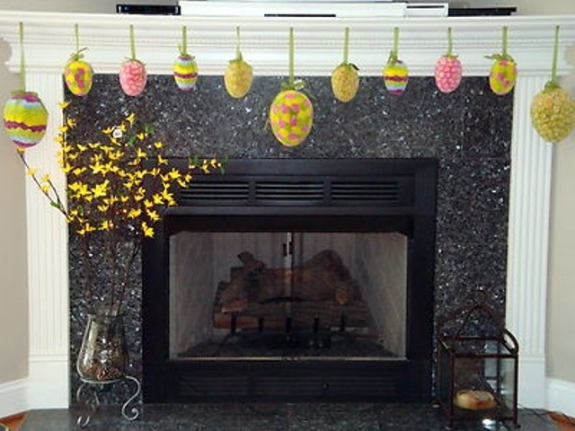 colorful paper Easter eggs hanging on the mantel and blooming branches in vases