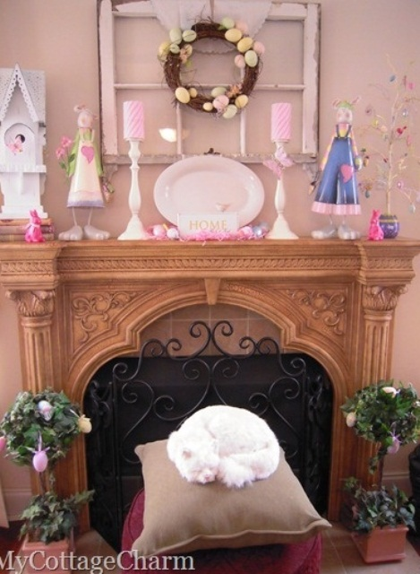 a funny Easter mantel a fake bird house, colorful candles, an Easter tree and an egg wreath