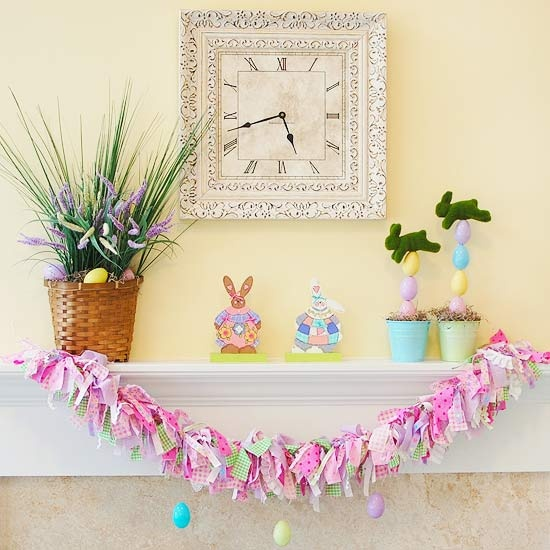 a colorful bunting, colorful faux eggs and moss bunnies and blooms and grass in pots
