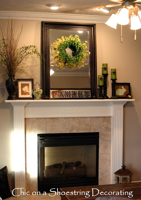 a spring Easter mantel with green candles, a jar with green eggs, some signs, blooming branches in vases