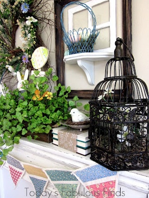 vintage Easter mantel decor with a cage, some baskets and fake birds, potted greenery and a wreath