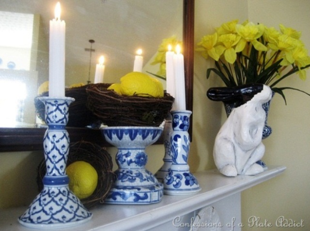 a bright Easter mantel with a floral arrangement, a nest with lemons and blue candle holders