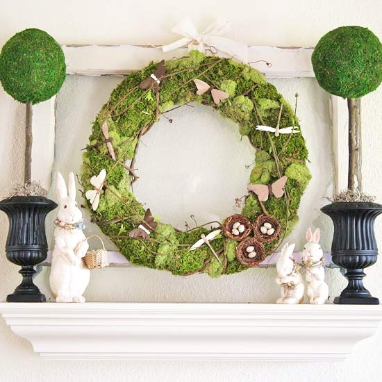 a fresh Easter mantel with moss topiaries, a moss wreath with butterflies and nests and bunnies