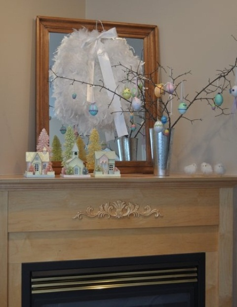 a pastel Easter mantel with an Easter tree and eggs hanging on it, a feather wreath and eggs hanging down