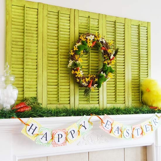 a bright Easter mantel with green shutters, some grass, carrots, a toy chick and a bunting