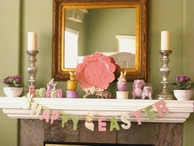 a pastel Easter mantel with a bunting, fake bunnies, potted blooms and plates