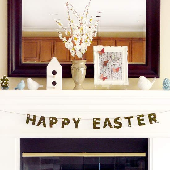 a neutral Easter mantel with fake birds, fake eggs, a butterfly artwork and blooming branches