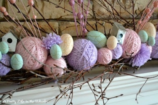 a colorful Easter mantel with fake eggs and yarn balls, with branches and a bird house