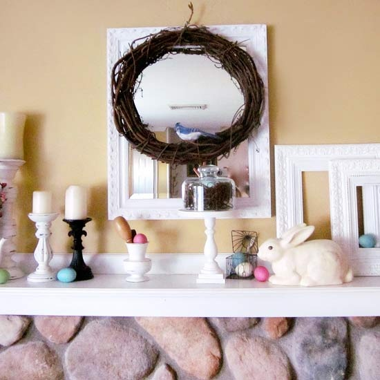 a bright Easter mantel with fake bunnies, colorufl eggs, a wreath with a bird and candles