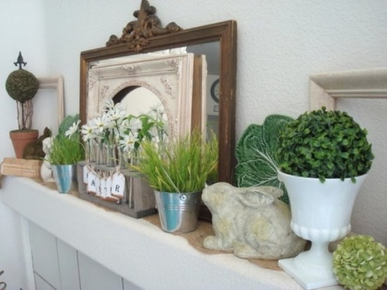 a fresh spring mantel with boxwood topiaries, potted grass and blooms, fake bunnies