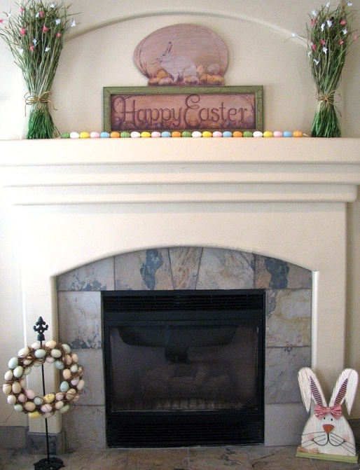 colorful faux eggs on the mantel and ina  wreath, an Easter sign and fake greenery with butterflies